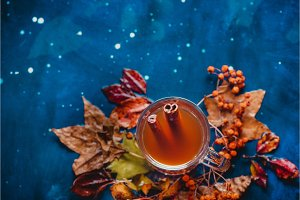 Tea cup with anise stars and cinnamon on a wet autumn background with fallen leaves and berries. Rainy day concept with copy space.