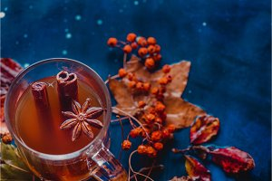 Tea with cinnamon in an autumn still life with fallen leaves and ash berry on a wet wooden background. Seasonal concept with copy space.