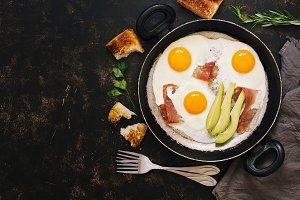 Breakfast with avocado, fried eggs, bacon, toast. Dark rustic background, top view, copy space.