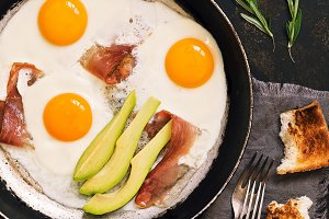 Fried eggs with bacon are served in a frying pan with avocado. A delicious hearty breakfast in a rustic style on a dark background. View from above.