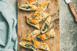 Freshly baked Turkish borek roll cut in slices, concrete background