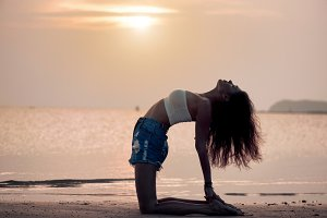 Young woman practicing yoga on the beach at sunset