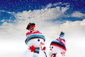 two snowman in snow