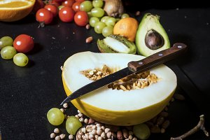 sliced melon and avocado with tropical fruits on dark surface with knife