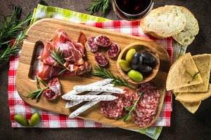 Antipasto - sliced meat, ham, salami, olives on dark stone table
