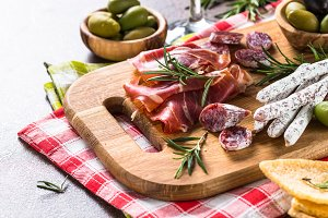 Antipasto delicatessen - sliced meat, ham, salami, olives on woo