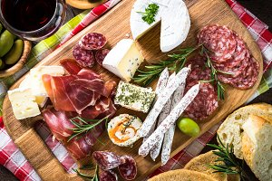 Antipasto - sliced meat, ham, salami, cheese, olives on wooden b