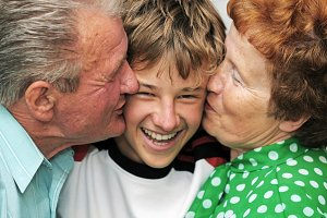 Grandparents kissing their grandson