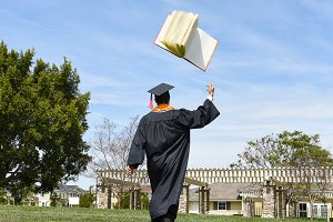 Graduate Tossing Book in the Air