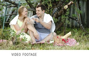 Young couple on picnic drinking wine