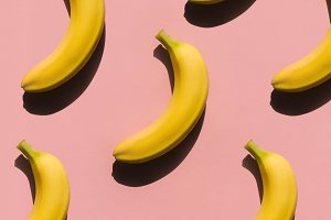 Ripe bananas on pink surface