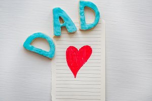 Postcard with painted red heart and word DAD