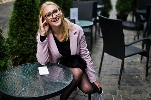 Blonde girl at glasses and pink coat