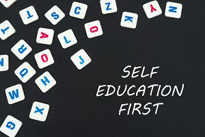 english colored square letters scattered on black background with text self education first