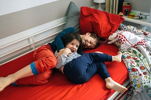 Brothers tickling and laughing lying on the bed