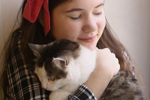 teenager pretty girl cuddling with pet cat
