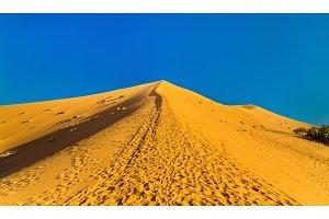 Climbing a dune near Merzouga in Morocco