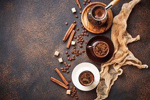 Cups of coffee, beans, sugar and cinnamon