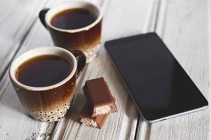 Two coffee mugs and a chocolate bar