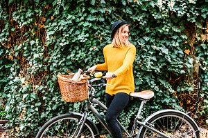 Young woman with bicycle in sunny spring nature.