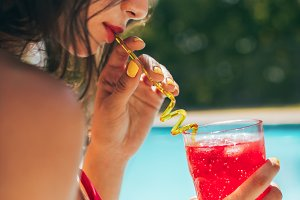 Woman drinking cocktail at the pool