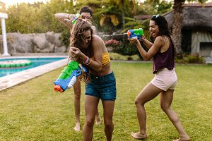 Happy friends doing water gun battle
