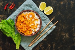 Rice and shrimp with curry sauce. Traditional Thai dish on a dark background. Asian food. Top view, copy space.