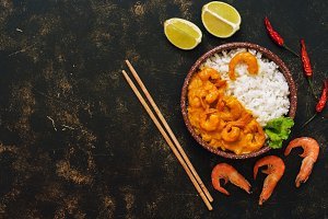 Rice with shrimps in curry sauce on a dark rustic background. The concept of Asian food. Top view, copy space.