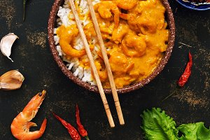 Asian food, shrimp in curry sauce with rice on a dark background.
