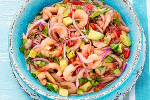 MEXICAN FOOD. Mexican shrimps ceviche sebiche with tomatoes and avocado in blue bowl, wooden blue background. Top view