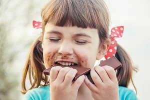 A sweet-toothed child eats chocolate