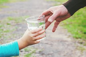 The father gives the child a glass