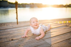 A child a boy, one year old, blond man lies on his stomach on wooden dock, pier in striped clothes, compound near pond on sandy beach against background of river in the summer at sunset of the day