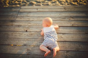 Newborn child A boy, one year old, is lying on his stomach on a wooden dock, a pier in striped clothes, a top view, a summer compline in the sunset of the day. Theme of a summer family vacation