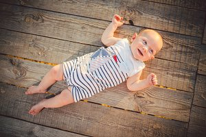 Newborn baby boy one year blond lying on his back on a wooden background wharf, pier in striped clothes view from above, compineison in summer at sunset of the day. Theme of a summer family vacation