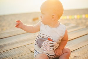 Child boy one year blond sits on a wooden dock, a pier in striped clothes, a compound near the pond on a sandy beach against a background of a river in the summer at sunset of the day