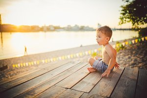 The theme is child and summer beach vacation. A small Caucasian boy sits sideways on a wooden pier and admires the view of the sandy beach and the pond, the river. With bare legs in blue denim shorts