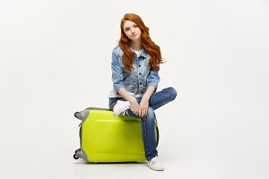 Ready for vacation. Traveling concept. Young excited caucasian woman sitting on the luggage. Isolated on white.