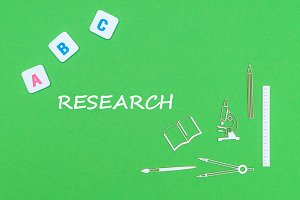 text research, from above wooden minitures school supplies and abc letters on green background