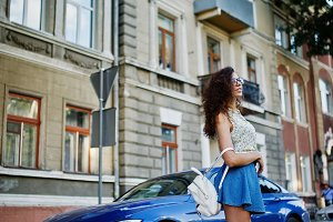 Curly stylish girl in blue skirt