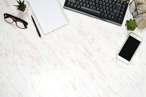 Flat lay office marble desk with phone, keyboard and notebook copy space background