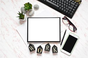 Flat lay office marble desk with phone, keyboard and notebook, frame for text space background