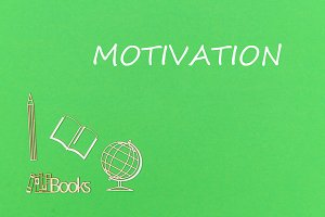 text motivation, school supplies wooden miniatures on green background