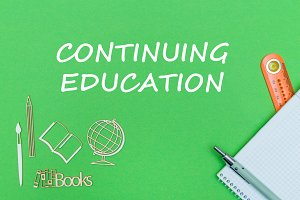text continuing education, school supplies wooden miniatures, notebook on green background