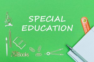 text special education, school supplies wooden miniatures, notebook with ruler, pen on green backboard