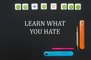 Black art table with stationery supplies with text learn what you hate on blackboard