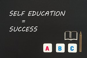 abc letters and chipboard miniature on blackboard with text self education success