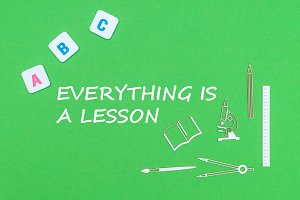 text everyting is a lesson, from above wooden minitures school supplies and abc letters on green background