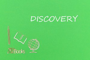 text discovery, school supplies wooden miniatures on green background
