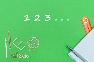 numbers 123, school supplies wooden miniatures, notebook on green background